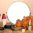 Round table mirror with cosmetics on table on beige background — Stock Photo #40391307