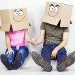 Couple with cardboard boxes on their heads sitting on floor near wall — Stock Photo #40391859