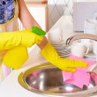 Beautiful young womcleans in kitchen — Stock Photo #40392319