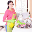 Beautiful young womcleans in kitchen — Stock Photo #40392323