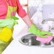 Beautiful young womcleans in kitchen — Stock Photo #40392327