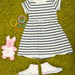 图库照片: Beautiful dress and gumshoes for little girl on green carpet