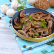 图库照片: Delicious fried mushrooms in pon table close-up