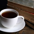 Cup of hot tea with books on table close up — Stock Photo #40393521