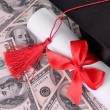 Stock fotografie: Graduation hat and scroll on money background