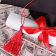 Stock Photo: Graduation hat and scroll on money background