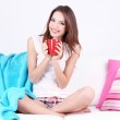Beautiful young woman sitting on sofa with red cup on gray background — Stock Photo #40394903
