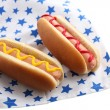 Stock fotografie: Tasty hot dogs on napkin with stars, isolated on white