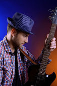 Young musician playing guitar on dark color background — Stock Photo