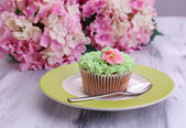 Tasty cupcake with butter cream, on plate, on color wooden background — Stock Photo