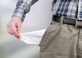 Man showing his empty pocket on bright background — Stock Photo