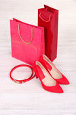 Mooie rode vrouwelijke schoenen, riem en winkel tassen — Stockfoto