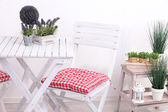Garden chair and table with flowers on wooden stand on white background — Stock Photo