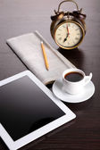 Tablet, newspaper, cup of coffee and alarm clock on wooden table — Stock Photo