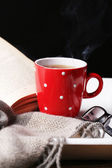 Cup of hot tea with book and plaid on table on dark background — Stock Photo