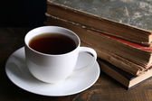 Cup of hot tea with books on table close up — Stock Photo