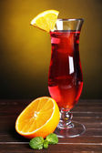 Glass of cocktail on table on dark yellow background — Stock Photo