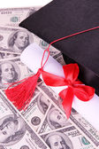 Graduation hat and scroll on money background — Stock Photo