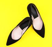 Beautiful black female shoes, on yellow background — Stock Photo