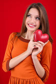 Attractive woman with heart, on red background — Stock Photo