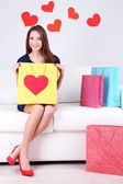 Beautiful young woman sitting on sofa with shopping bags on gray background — Stockfoto