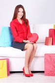 Bella mujer joven sentada en el sofá con bolsas de compras y caja de regalo sobre fondo gris — Foto de Stock