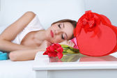 Beautiful young woman sleeping on sofa near table with gifts and flowers, close up — Foto de Stock