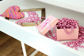 Gift box and beads in open desk drawer close up — Stock Photo