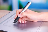 Female hand using graphics tablet on table on bright background — Stock Photo