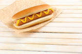 Tasty hot dog on wooden table — Stock Photo