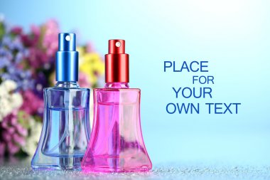 Women perfume in beautiful bottles and flowers on blue background