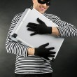 Stock Photo: Thief with metal briefcase on dark background