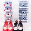 Stock fotografie: Shoes in plastic boxes and female shoes on floor in room