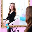 Stock Photo: Young beautiful womsitting front of mirror in room