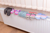Knitted gloves drying on heating radiator — Stock Photo