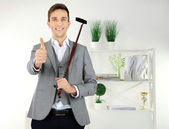 Elegant young businessman playing mini golf at home — Stock Photo