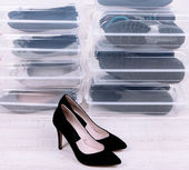 Shoes in plastic boxes and female shoes on floor in room — Stock Photo