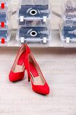 Scarpe donne scarpe sul pavimento in camera e scatole di plastica — Foto Stock