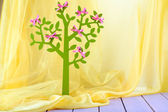 Decorative tree with bows, on wooden table on color fabric background — Stock Photo