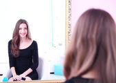 Young beautiful woman sitting front of mirror in room — ストック写真
