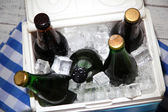 Ice chest full of drinks in bottles on color napkin, on wooden background — Stock Photo