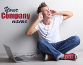 Handsome young man listening to music on grey background — Stock Photo