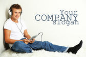 Young man relaxing on carpet and listening to music, on gray wall background — Stock Photo