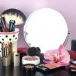 Round table mirror with cosmetics and flower on table on violet background — Stock Photo #40512021