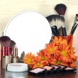 Round table mirror with cosmetics and flowers on table on wooden background — Stock Photo #40512035