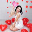 Stock Photo: Attractive young woman read card in decorated room on Valentine Day