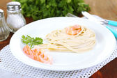 Pasta with shrimps on white plate, on wooden background — Stock Photo