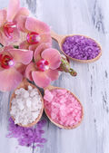 Still life with beautiful blooming orchid flower and wooden spoons with sea salt, on color wooden background — Стоковое фото