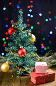 Decorative Christmas tree with gifts on table on bright background — Stock Photo