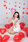 Attractive young woman read card in decorated room on Valentine Day — Stock Photo